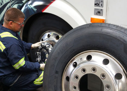 Service technician changing a tire on a large bus.