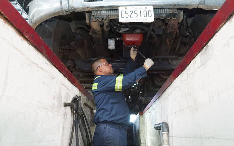 Service technician repairing a bus.